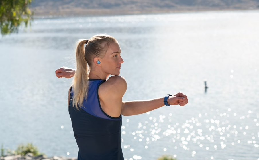 Vrouw bij een meer met JBL Reflect Flow oortjes in.